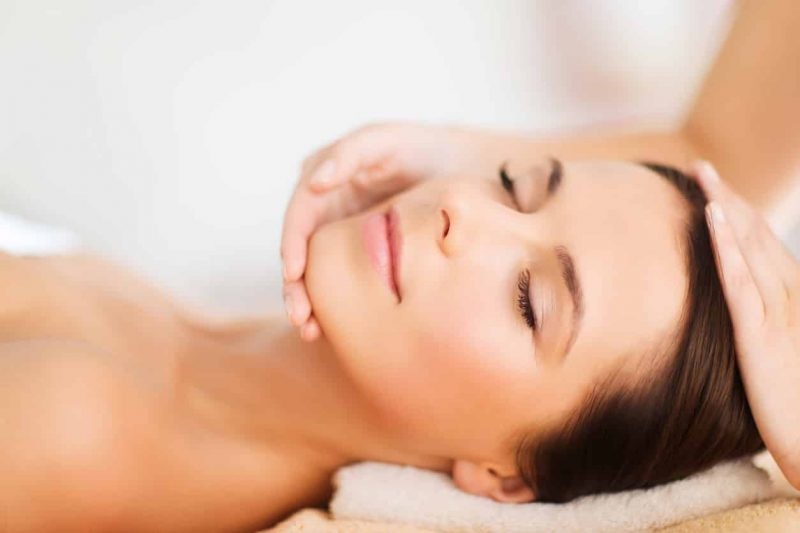 spa, people, beauty and health concept - beautiful woman in spa salon getting face treatment or facial massage